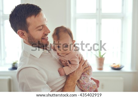 Proud father holding his newborn baby daughter in his at home - stock photo