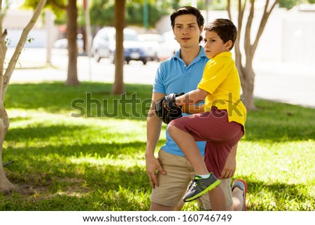 Proud father watching his son practice baseball at a park - stock photo