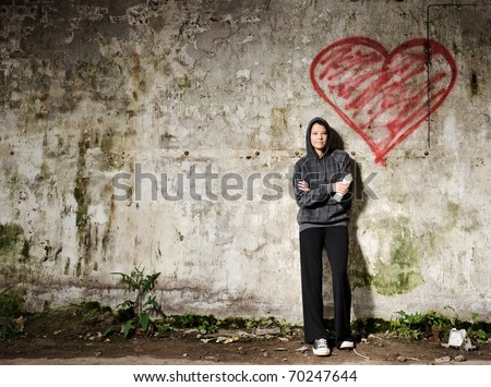 Proud graffiti girl stands with her valentine heart - stock photo
