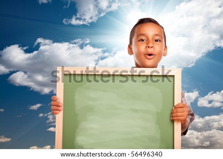 Proud Hispanic Boy Holding Blank Chalkboard Over Blue Sky and Clouds with Sun Burst. - stock photo