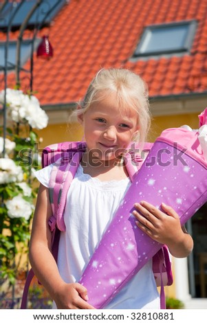 Proud kid having first day at school holding a traditional cone filled with sweet stuff - stock photo