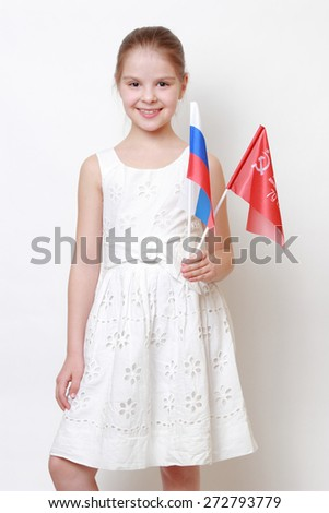 Proud little girl holding national flag of Russian Federation (Russia) and Victory Banner - Assault flag of the 150th Order of Kutuzov II Degree Idritsa Infantry Division in the second World War  - stock photo