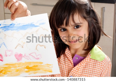 Proud little girl showing her painting - stock photo