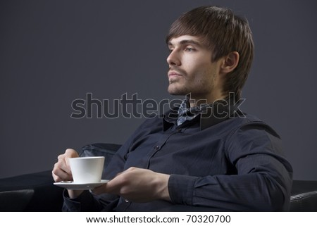 proud man in elegant dress holding cup coffee - stock photo