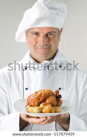 Proud mature chef serving a roast chicken with potatoes - stock photo