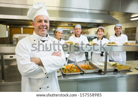 Proud mature head chef posing in a modern kitchen with his colleagues in the background - stock photo