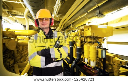 Proud mechanic, posing with his arms crossed, a hard hat, goggles, gloves and a reflective coat in the engine room of an industrial offshore supply ship - stock photo