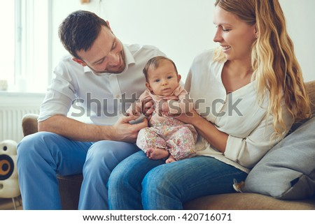 Proud mother and father smiling at their newborn baby daughter, sitting on the sofa at home