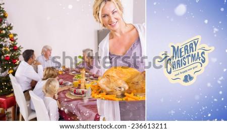 Proud mother showing roast turkey against purple vignette - stock photo
