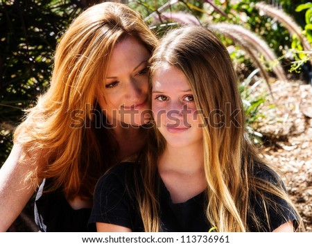 Proud mother with pretty teen daughter - stock photo