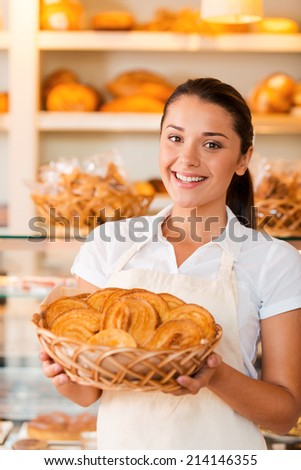 Proud of her baked goods. Beautiful young woman in apron holding basket with baked goods while standing in bakery shop - stock photo