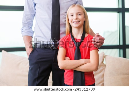 Proud of her father. Cheerful little girl in necktie standing near her father and keeping arms crossed  - stock photo