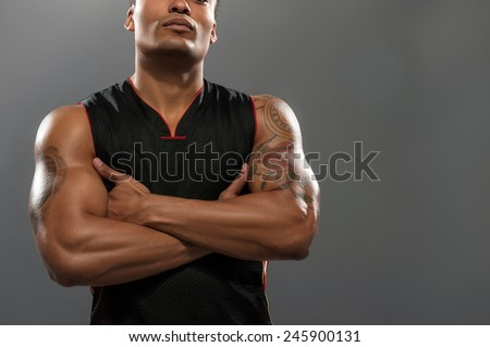 Proud of his fit body. Cropped image of young shirtless African man looking up and keeping arms crossed while standing against grey background - stock photo