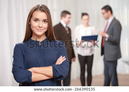 Proud of my business. Confident smiling female manager standing with her arms crossed on a chest while her colleagues are standing on the background in blurry - stock photo