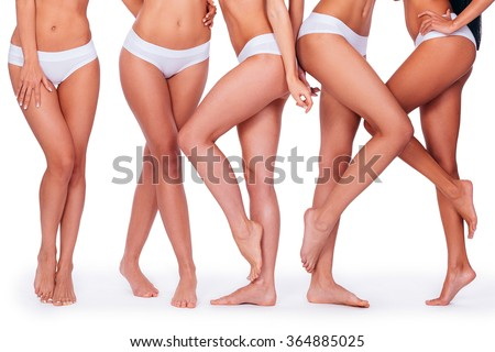 Proud of their perfect legs. Close-up of five women in white panties showing their perfect legs while standing against white background