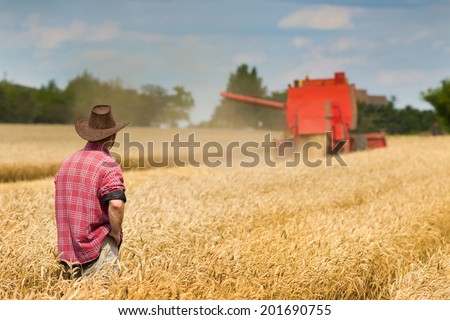 Proud old peasant standing on field with combine in background - stock photo