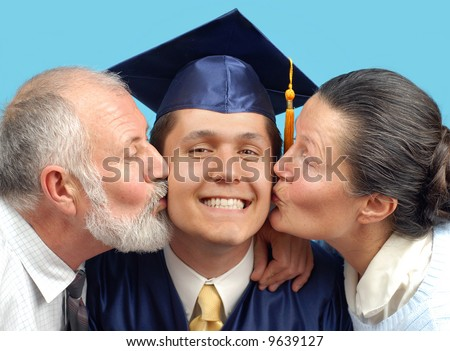 Proud parents kissing their graduating son on both cheeks