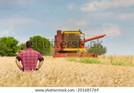 Proud peasant standing on field with combine in background - stock photo
