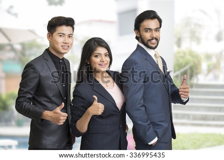 Proud smiling business people showing success sign at office background. - stock photo