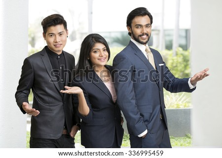 Proud smiling Indian business people gesturing at office - stock photo