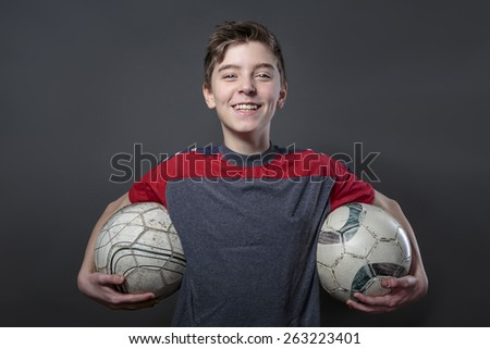 proud, smiling teenage boy holding two soccer ball's, with colored spotlights and stadium in background - stock photo