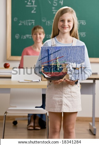 Proud student holding art project in school classroom