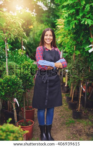 Proud successful confident young nursery owner standing in her greenhouse between the rows of potted plants with folded arms smiling at the camera