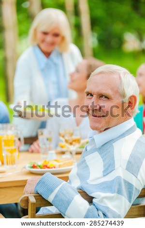 Proud to have a big family. Happy family sitting at the dining table outdoors while senior man looking over shoulder and smiling  - stock photo