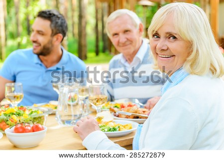 Proud to have a big family. Happy family sitting at the dining table outdoors while senior woman looking over shoulder and smiling  - stock photo