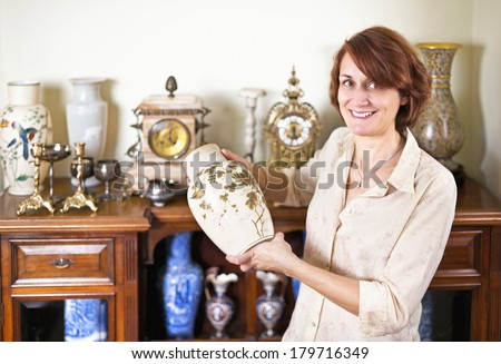 Proud woman holding vase from her collection of antiques - stock photo