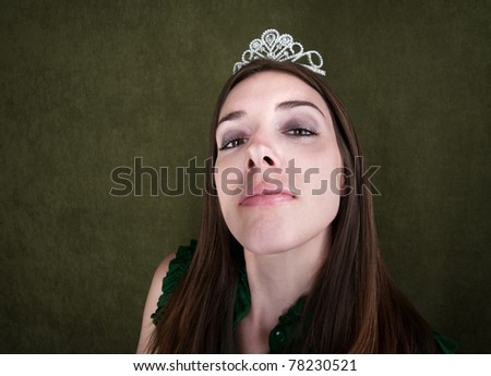 Proud woman with tiara on green background - stock photo