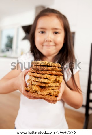 Proud young child with stack of freshly baked cookies - Shallow DOF, focus on cookies - stock photo