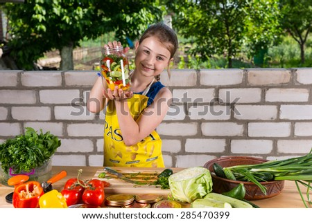 Proud young girl showing off her bottled vegetables in a glass jar that she is busy preparing at an outdoor table with a large variety of food - stock photo