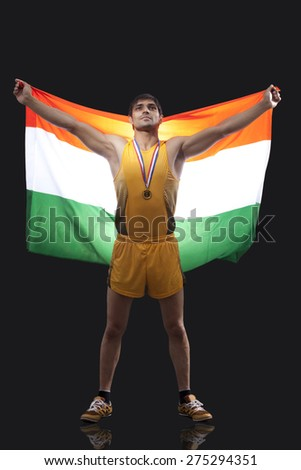 Proud young medalist with Indian flag standing against black background - stock photo