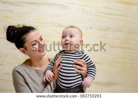 Proud young mother with her baby son held aloft in her arms grinning joyfully at the camera, with copyspace - stock photo