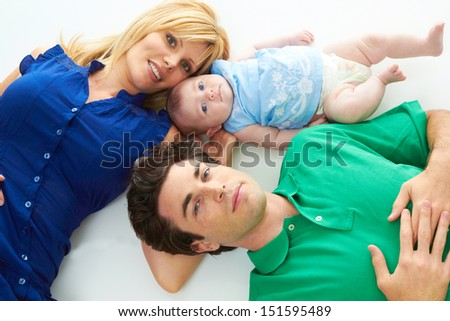 Proud young parents laying down with baby girl isolated on white background - stock photo