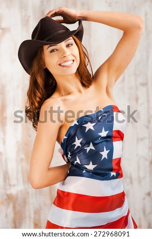 Proudly American. Beautiful young shirtless cowgirl adjusting her hat and covering herself by American flag while standing against the wooden background