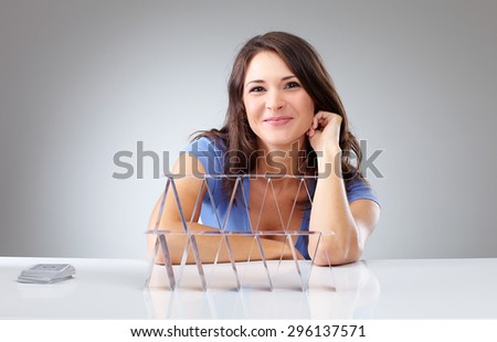 Proudly young woman with a house of cards on isolated background - stock photo