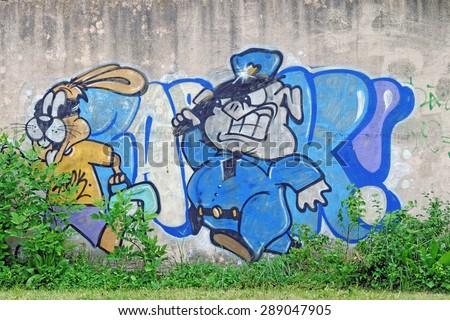Provadia, BULGARIA - May 16, 2015: Street art by unknown artist of a pig policeman in action chasing a runaway rabbit.  - stock photo