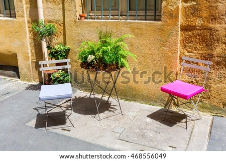 Provencal scene with folding chairs in front of a house