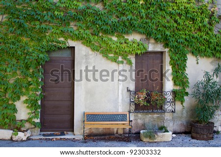 Provence, France: House covered by vegetation and a bench - stock photo