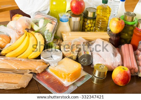 Provision with vegetables and meat for moderate family at table in home - stock photo