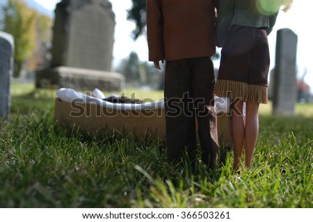 Provo, UT, USA - November 7, 2004: Barbie dolls attend a funeral.  Ken lays in a pine box in a brown suite.