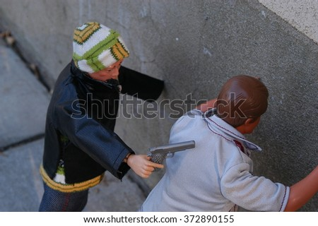 Provo, Utah, USA - 4 December 2004: Classic Ken doll and vintage GI Joe action figure posed outside to illustrate gun violence in America concept.  Mugging by a hand gun. - stock photo
