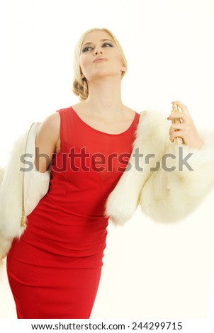 provocative boudoir style portrait of a Young sensual blond girl wearing a red dress and White fur coat putting a perfume on her perfect long neck isolated on white - stock photo