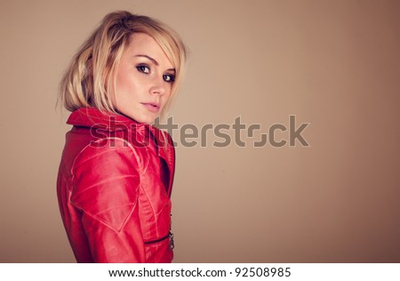 Provocative Fashionable Blonde Woman dressed in a leather jacket and glancing sideways at the camera with raised eyebrow. - stock photo