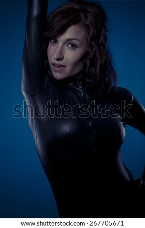 Provocative, sexy brunette in black latex bodysuit tight and wild poses - stock photo