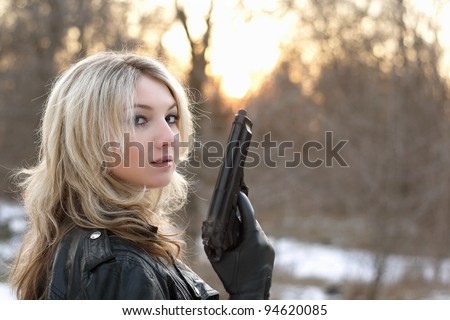 Provocative young woman holding a gun in winter forest - stock photo