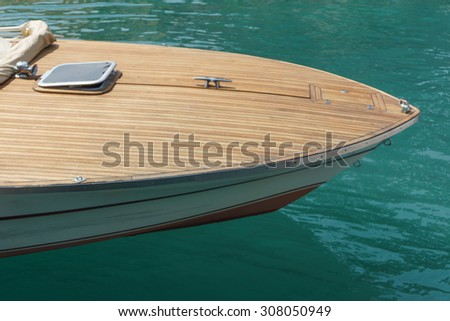 Prow of a motorboat or speedboat with a wood finish moored in a harbor in sheltered water, high angle close up view - stock photo