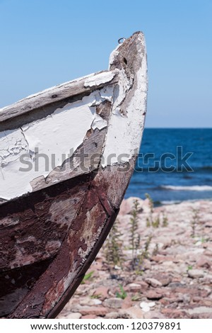Prow of an old wooden boat with peeling flaking paint beached on a stony beach near the ocean - stock photo